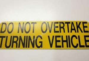 Rear DO NOT OVERTAKE TURNING VEHICLE signs